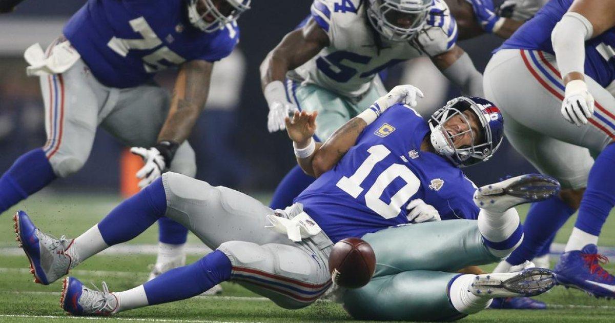 Eli Manning gets sacked. Photo Credit: bloggingtheboys.com