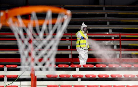 A person cleans the seats of an empty stadium with no fans inside and no sports going on at the time